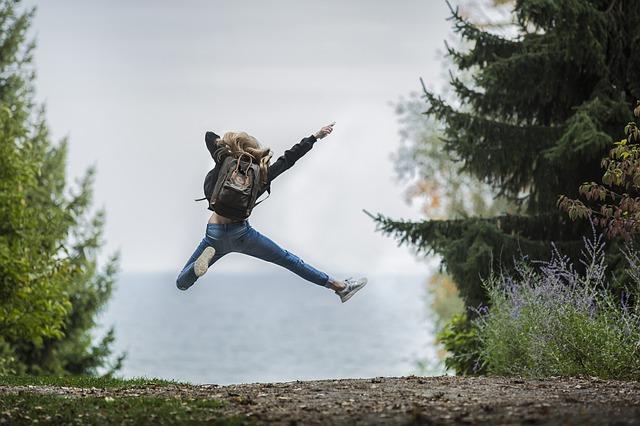 ジャンプして喜ぶ女性の後ろ姿