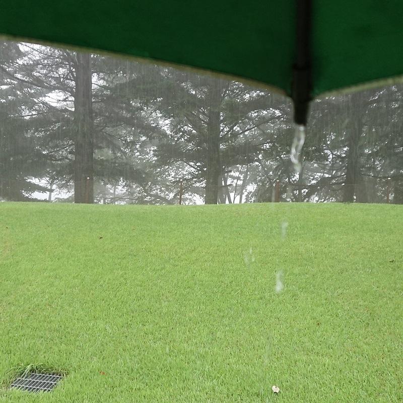 豪雨で傘から滴り落ちる水滴
